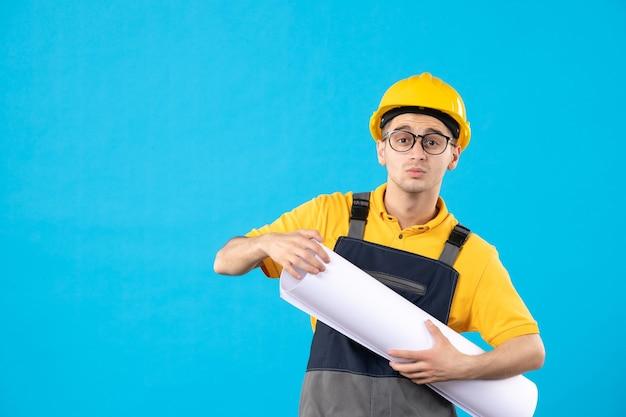 青の紙の計画と制服を着た正面図の男性ビルダー
