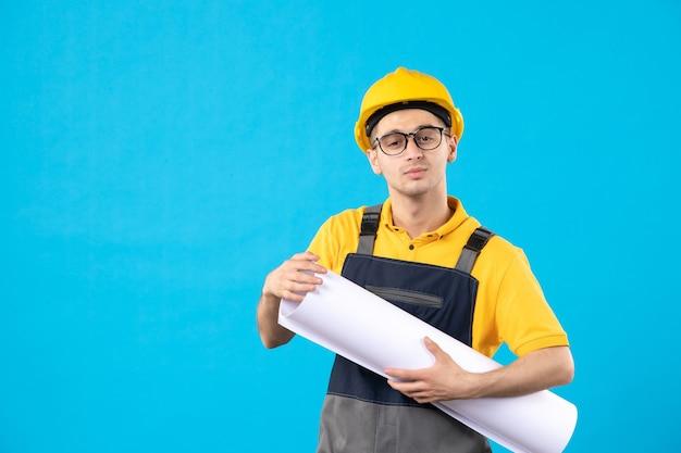 Мужчина-строитель в униформе с бумажным планом на синем, вид спереди