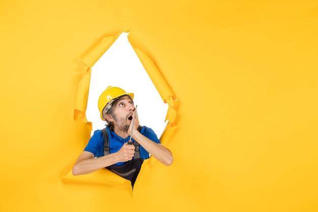 노란색 벽 작업 생성자 건물 색상 작업자 아키텍처 작업에 스크루드라이버가 있는 유니폼을 입은 전면 보기 남성 빌더
