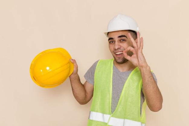 明るい背景に黄色いヘルメットを保持している白いヘルメットの正面男性ビルダー