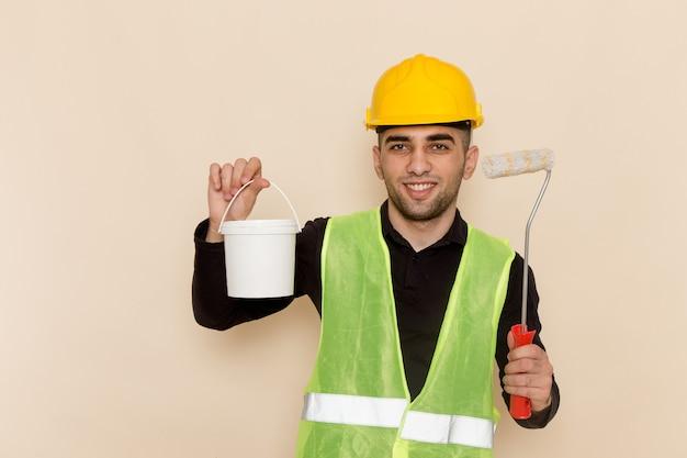 クリーム色の背景にペイントとブラシを保持している黄色いヘルメットで正面男性ビルダー