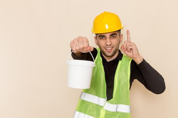 Вид спереди мужчина-строитель в желтом шлеме, держащий краску с поднятым пальцем на светлом столе