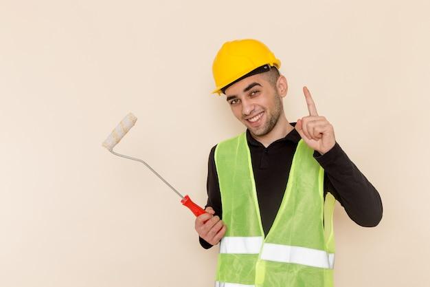 Вид спереди мужчина-строитель в желтом шлеме, держащий стенную щетку на светлом фоне