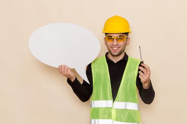 明るい背景に白い看板とツールを保持している黄色いヘルメットの正面男性ビルダー