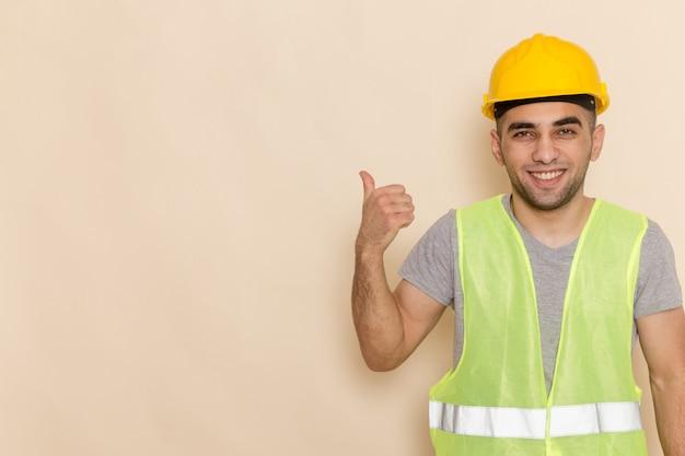 明るい背景に笑顔でポーズ黄色のヘルメットの正面男性ビルダー