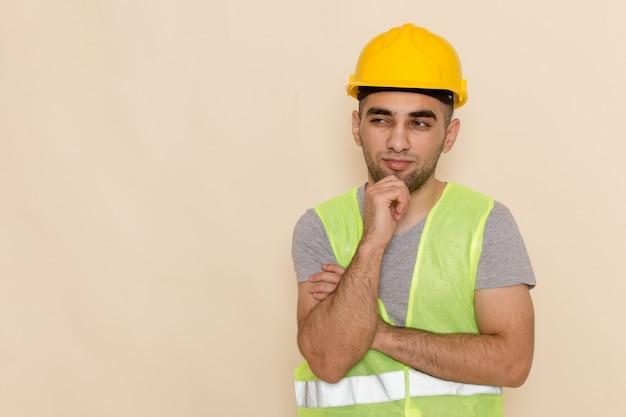 Вид спереди мужчина-строитель в желтом шлеме позирует с выражением мышления на светлом фоне