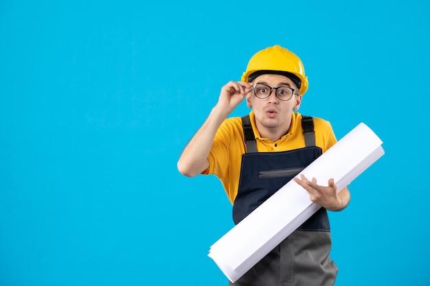 Вид спереди мужчина-строитель в желтой форме с бумажным планом на синем