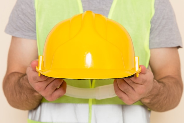 Front view male builder taking off yellow helmet on the light background