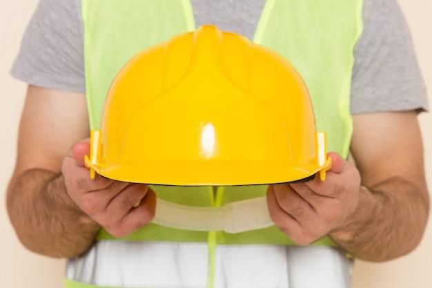 Мужчина-строитель, снимающий желтый шлем на светлом фоне, вид спереди