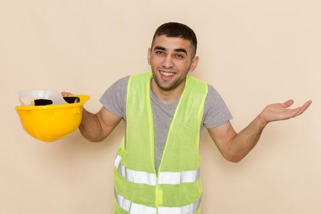 Вид спереди мужчина-строитель, снимающий желтый шлем, позирует с улыбкой на светлом фоне