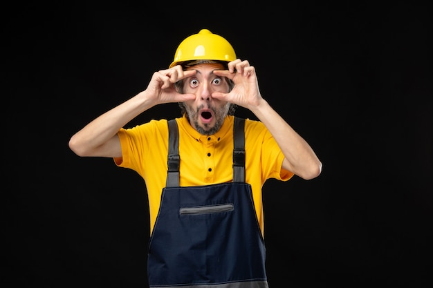 Front view of male builder in uniform on black wall