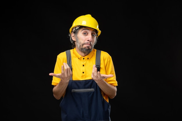 Front view male builder in uniform on black wall