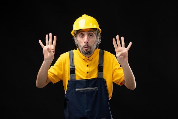 Vista frontale del costruttore maschio in uniforme sul muro nero