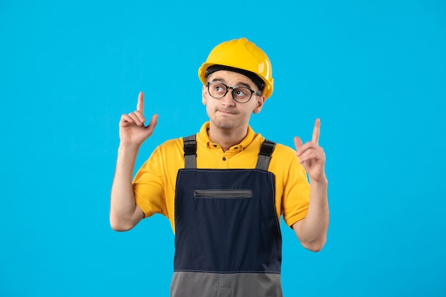 Front view of male builder in uniform on blue wall