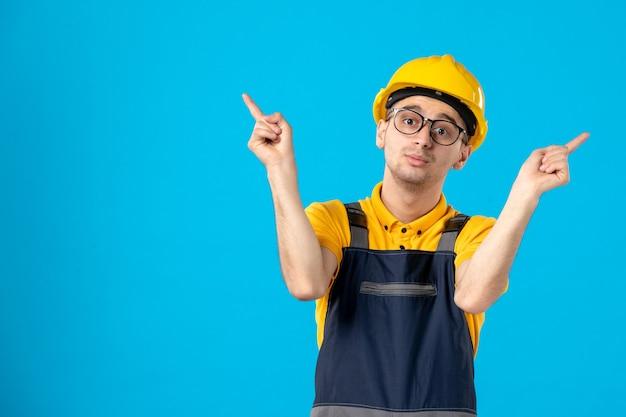 Vista frontale del costruttore maschio in uniforme sulla parete blu