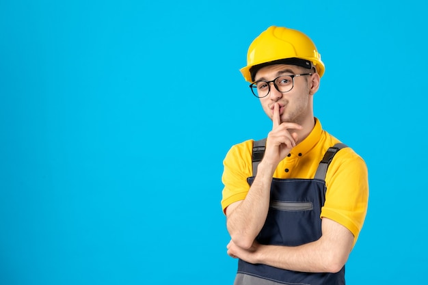 Front view male builder in uniform and helmet asking to be quiet on blue