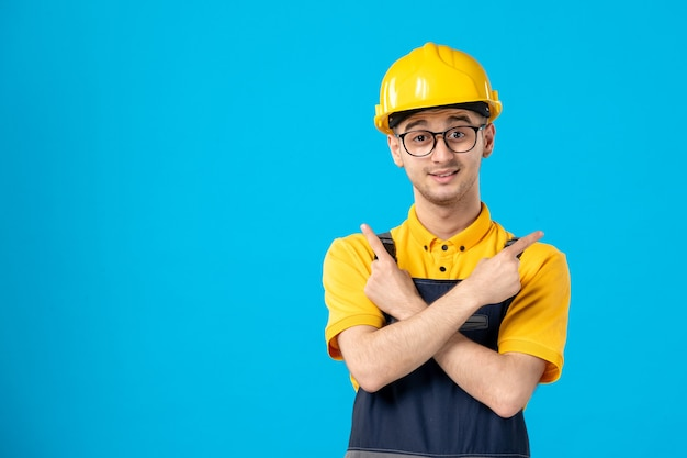 Front view of male builder in uniform and helmet on blue surface