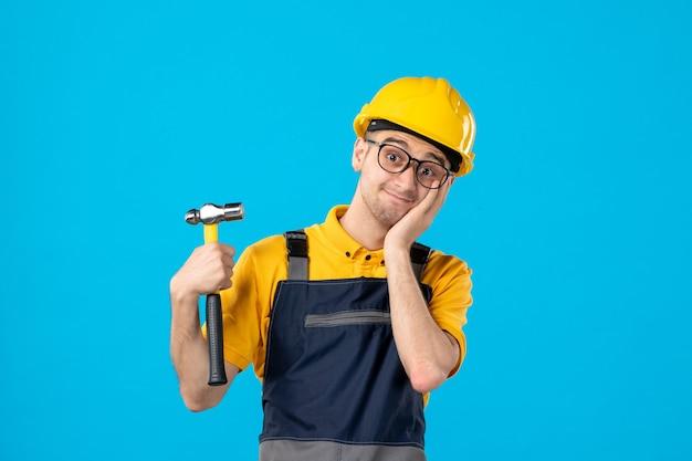Vista frontale del costruttore maschio in uniforme e casco sulla superficie blu