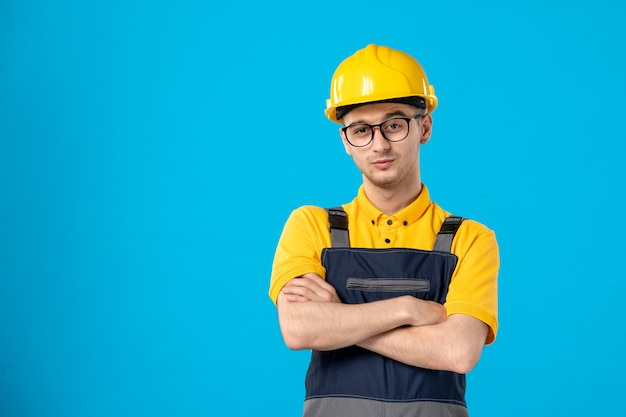 Front view of male builder in uniform and helmet on blue wall