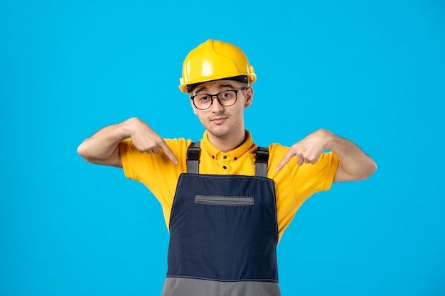 Vista frontale del costruttore maschio in uniforme e casco sulla parete blu