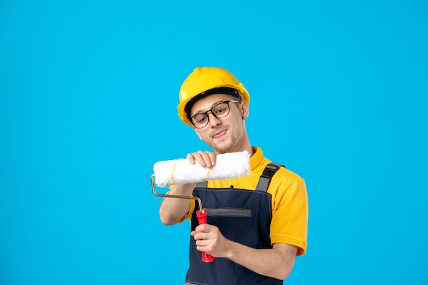 Front view male builder in uniform and helmet fixing paint roller on a blue
