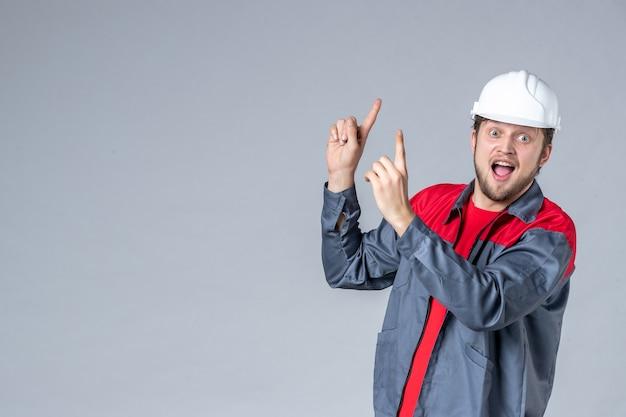 Costruttore maschio vista frontale in uniforme e casco su sfondo grigio