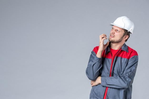 Costruttore maschio vista frontale in uniforme e casco su sfondo grigio Foto Gratuite
