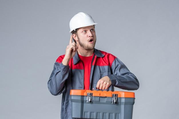 Vista frontale costruttore maschio in uniforme e casco che tiene la valigetta degli attrezzi su sfondo grigio