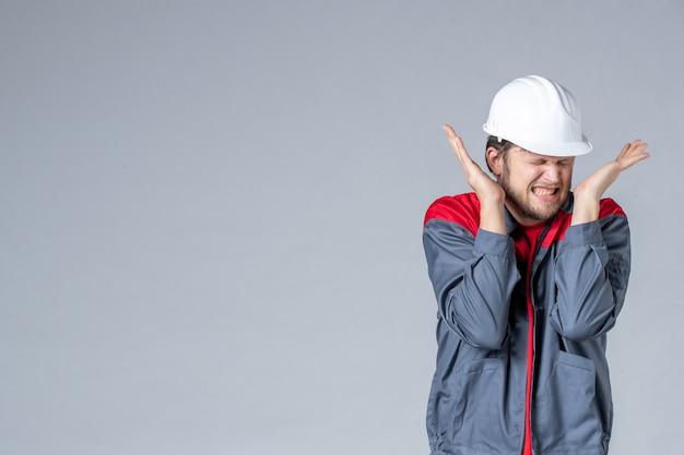 Costruttore maschio vista frontale in uniforme e casco su sfondo chiaro