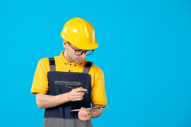 Vista frontale del costruttore maschio in uniforme e casco che prende appunti sulla parete blu
