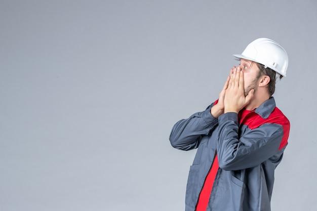 Costruttore maschio vista frontale in uniforme e casco spaventato su sfondo grigio