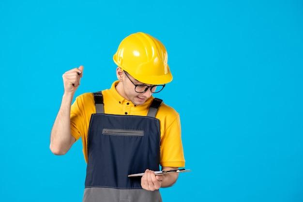 Vista frontale del costruttore maschio in uniforme e casco prendendo appunti sulla parete blu