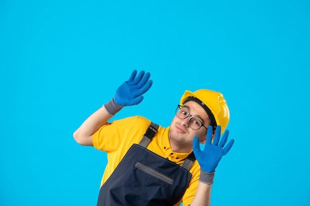 Vista frontale del costruttore maschio in uniforme e casco con i guanti sulla superficie blu