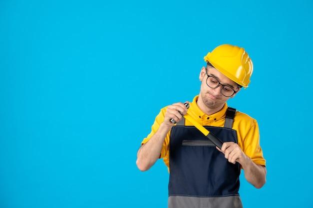 Vista frontale del costruttore maschio in uniforme e casco con martello sulla parete blu