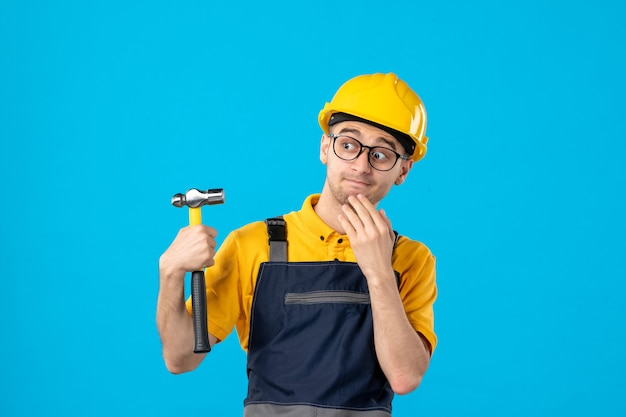 Front view male builder in uniform and helmet with hammer on blue