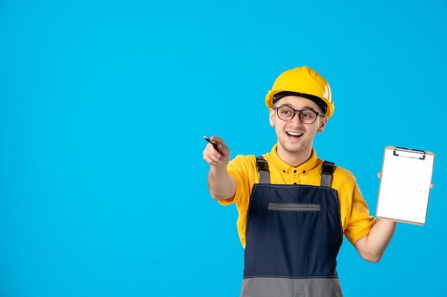 Vista frontale del costruttore maschio in uniforme e casco con blocco note sulla parete blu