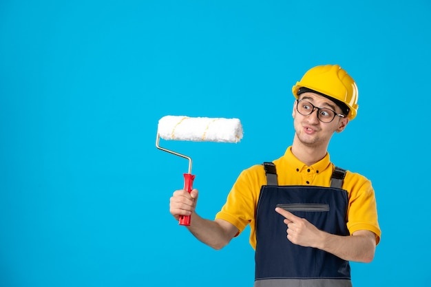 Front view male builder in uniform and helmet with paint roller on blue
