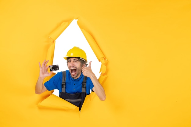 Front view male builder in uniform holding black bank card on yellow background