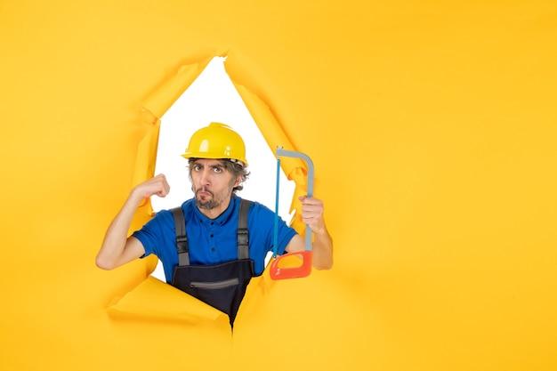 Costruttore maschio di vista frontale in uniforme che tiene sega ad arco su fondo giallo