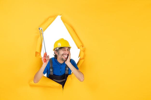 Costruttore maschio di vista frontale in uniforme che tiene sega ad arco su fondo giallo Foto Gratuite