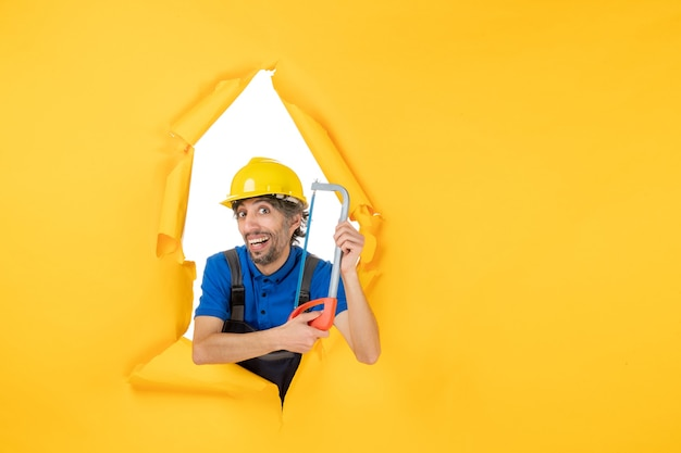 Front view male builder in uniform holding bowsaw on the yellow background