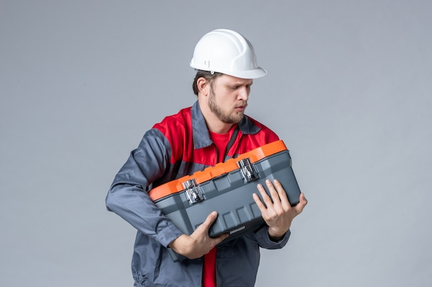 Costruttore maschio di vista frontale in uniforme che tiene cassetta degli attrezzi pesante su sfondo grigio