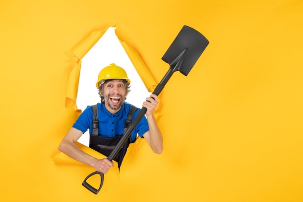Front view male builder in uniform holding shovel on yellow background