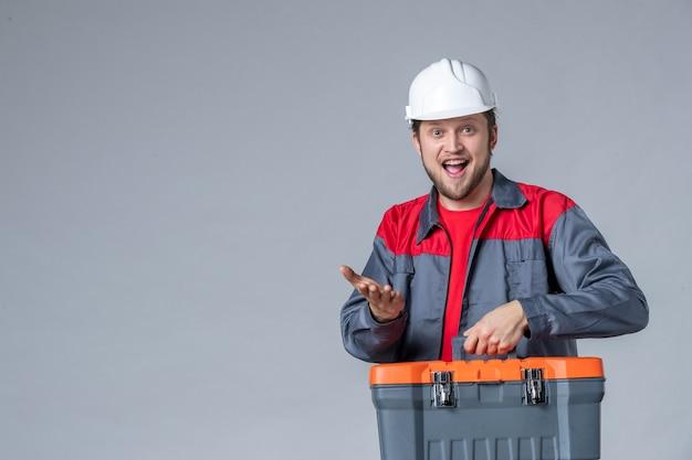 Costruttore maschio vista frontale in valigetta portautensili uniforme eccitato su sfondo grigio