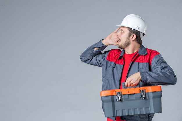 Front view male builder in uniform holding tool case on gray background