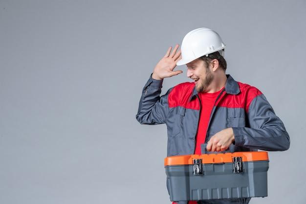 Vista frontale costruttore maschio in uniforme che tiene la valigetta degli attrezzi e ride su sfondo grigio
