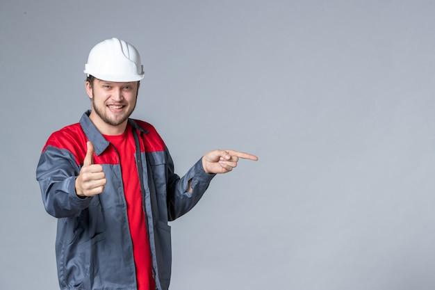 Costruttore maschio vista frontale in uniforme che mostra un gesto fantastico su sfondo chiaro
