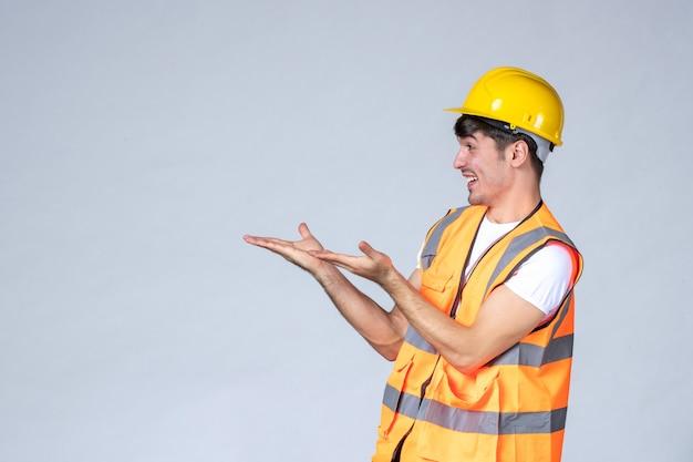 Vista frontale del costruttore maschio in uniforme che sorride a qualcuno sul muro bianco