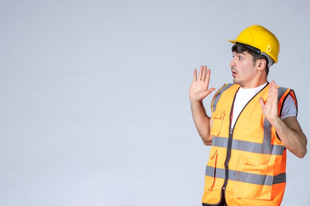 Front view of male builder in uniform talking to someone on white wall
