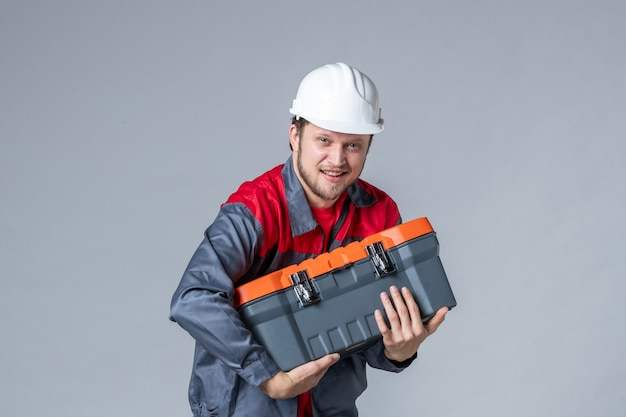 Front view male builder in uniform trying to open tool case on gray background